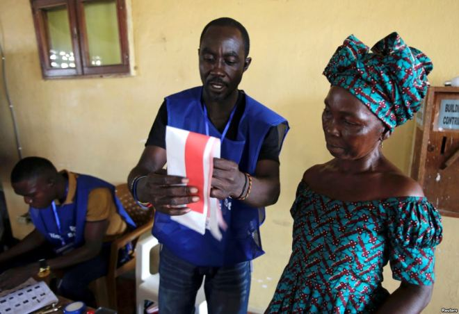 A Liberian Woman Being Helped to Cast her Vote